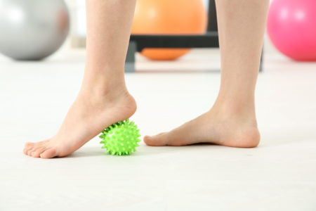 Feet of woman doing exercises with rubber ball in clinic
